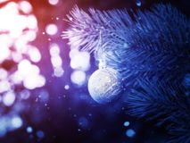 Silver Christmas Ball on a Branch. Decorative Christmas ball made of silver glitters on a spruce branch fantasy background Royalty Free Stock Photo