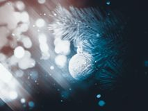 Silver Christmas Ball on a Branch. Decorative Christmas ball made of silver glitters on a spruce branch fantasy background Stock Photo