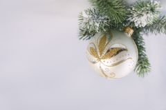 1 silver Christmas ball with a Golden pattern with a green spruce branch on a gray blue background, side view. 1 silver Christmas ball with a Golden pattern with stock photos