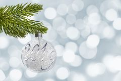 2019 on a silver christmas ball hanging from a branch bokeh lights background. 2019, on a silver christmas ball hanging from a branch bokeh lights background royalty free stock photos