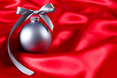 Silver christmas ball on a red silk cloth Royalty Free Stock Photo