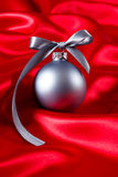 Silver christmas ball on a red silk cloth Royalty Free Stock Photos