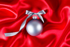 Silver christmas ball on a red silk cloth Stock Photography