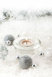 Silver christmas balls. With a burning candle on the snow stock photos