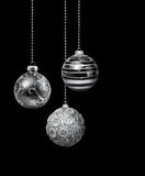 Silver Christmas balls. Three silver decoration Christmas balls hanging black background isolated royalty free stock photo