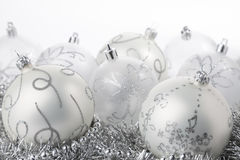 Silver christmas balls. Silver garland in front of many grey baubles with glitter royalty free stock photography