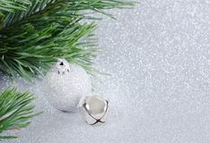 Silver Christmas balls and pine branch. Silver Christmas balls and pine branch on bright background royalty free stock images
