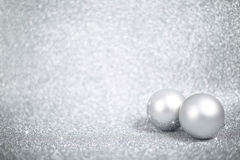 Silver christmas balls. On shiny glitter background close-up royalty free stock image