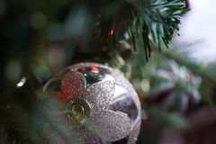 Silver Christmas Bauble Hanging on Christmas Tree stock photo