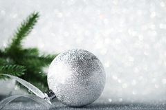 Silver christmas bauble. With ribbon and fir-tree branches on lights background Stock Image
