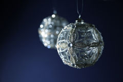 Silver Christmas Baubles. Two christmas balls in silver hanging on blue background. Selective focus stock image