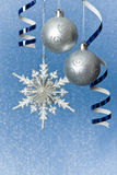 Silver Christmas baubles and snowflake. Silver Christmas baubles, snowflake  and  ribbon ornament on blue background of defocused  lights. Shallow DOF Stock Image