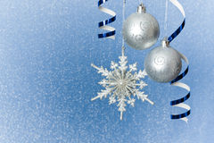 Silver Christmas baubles and snowflake. Silver Christmas baubles, snowflake  and  ribbon ornament on blue background of defocused  lights. Shallow DOF Stock Images