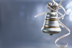 SIlver Christmas bell over blue background Stock Photo