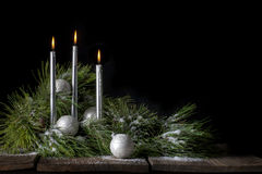 Silver Christmas Candles with Evergreen and Snow Royalty Free Stock Photography