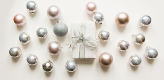 Silver Christmas decoration balls and gift on white. Top view. Xmas pattern stock photo