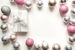 Silver Christmas decoration balls and gift on white. Space for text. Silver Christmas decoration balls and gift on white. Top view. Xmas pattern royalty free stock images