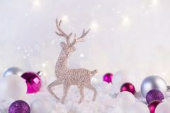 Silver christmas decoration deer and christmas balls on a pink winter background. Christmas holiday mood. Magic and fairy tale. Template, greeting card stock photography