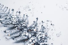 Silver Christmas decoration in sparkles and shiny shattered glass on a white background. Beautiful Christmas tree decoration in the form of a silver twig with stock photo