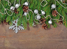 Silver Christmas decorations and spruce branch and cones on a wo Royalty Free Stock Image