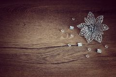 Silver Christmas flower. Laying on the wood background with beads around Royalty Free Stock Photography