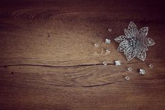 Silver Christmas flower. Laying on the wood background with beads around Stock Photo