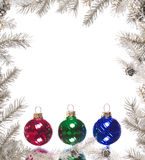 Silver Christmas frame with colorful baubles. Branches of a silver Christmas tree arranged with red, green and blue baubles to create a frame Royalty Free Stock Photos