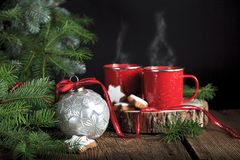 Silver Christmas Ornament with Hot Drinks. A silver Christmas ornament with snowflake design on old wooden surface with fresh evergreen boughs and two steaming royalty free stock image