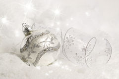 Silver Christmas Ornament in Snow. A silver Christmas ornament and curled snowflake patterned ribbon in snow. Stars and sparkles in background and foreground Royalty Free Stock Image