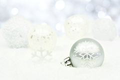 Silver Christmas ornaments in snow with twinkling background Royalty Free Stock Photography