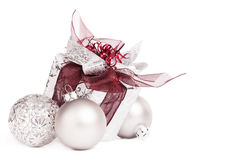 Silver christmas present with christmas balls. Silver christmas present with red ribbons and christmas balls on white background stock photos