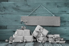 Silver christmas presents on wooden background with a sign. Silver christmas presents on wooden background with a sign for a bonus card stock images