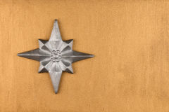 Silver Christmas star on gold background. Stock Photos