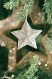 Silver Christmas star ornament hanging on Christmas tree Royalty Free Stock Photography