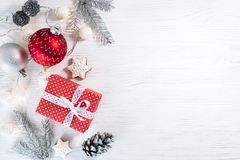 Christmas tree branches and red gift box with garland on wooden Royalty Free Stock Photography
