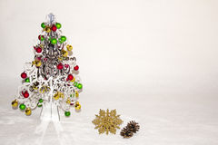 A silver Christmas tree with colourful decorations Stock Photos