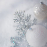 Silver Christmas tree decorations on snow. Silver Christmas tree decorations on real snow outdoors. Winter holidays concept. Shallow depth of fields Royalty Free Stock Image
