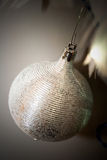 Silver Christmas Tree Ornament. Silver ball against lights white feathers and muted gray background Stock Photo