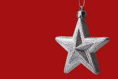 Silver christmas tree star on red background Stock Photography