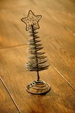 Silver Christmas tree and star on a wooden floor Stock Image