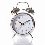 Silver chrome alarm clock with ringing bells. Traditional silver and chrome alarm clock, with big clear numerals and two alarm bells on top Stock Images