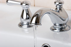 Silver chrome bathroom tap faucets running water Royalty Free Stock Image