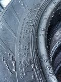 Black Wet Tire. A rubber suv tire covered in water droplets Royalty Free Stock Images