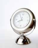 Silver clock. A brushed chrome clock on a stand showing the time approaching 4 o'clock. Studio lighting isolated on a white background Stock Image