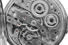 Silver Clockwork on white background. Detail of watch machinery. Old mechanical pocket watch. Macro shot. Stock Photos
