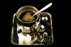 Silver Coffee Cup and Tray. Shiny metal cup filled with black coffee on a silver tray with roasted beans and sugar cubes on a black background stock photos
