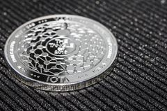 Silver coin cryptocurrency IOTA. MIOTA. On grey background royalty free stock photo