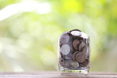 Silver coin in glass is placed on a wood floor with colorful bok Stock Photography