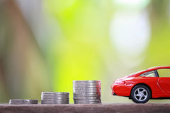 Silver coin of pile with red car model in concept savings to buy Stock Photography