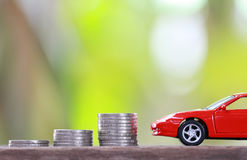 Silver coin of pile with red car model in concept savings to buy Royalty Free Stock Photos